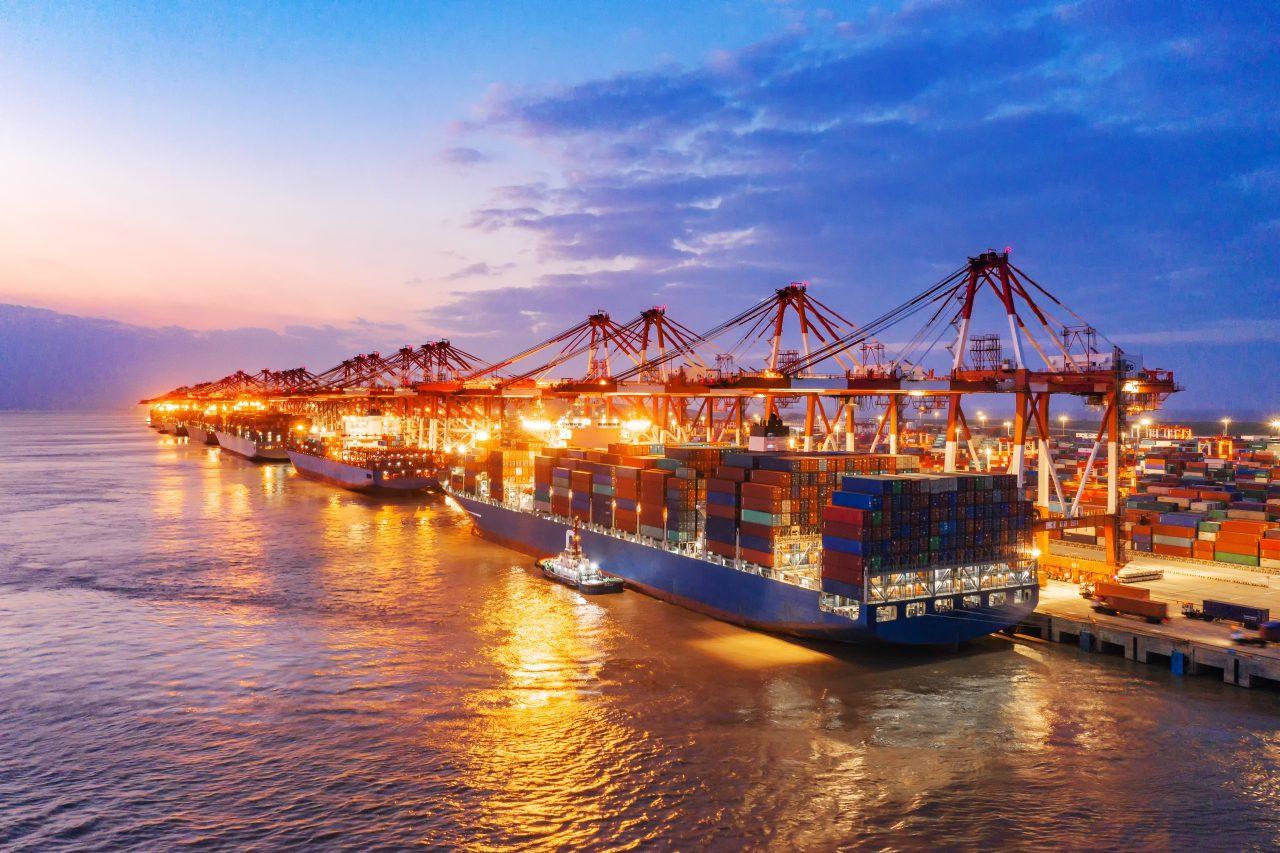 Transport morski z Chin. Statek towarowy stojący przy nabrzeżu podczas przeładunku z wykorzystaniem suwnic.