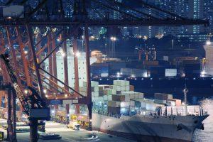 Transport Morski z Chin. Rozładunek kontenerowca na ciężarówki rozwożące kontenery do określonych terminali.